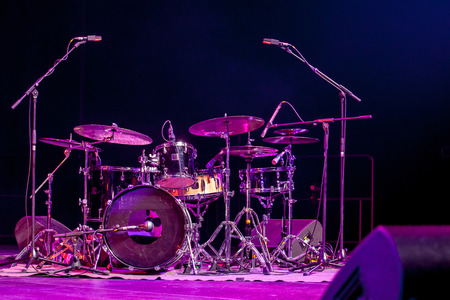 Drum kit on stage lit by red light Stock Photo