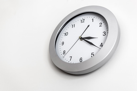 minutes: Clock hanging on wall showing twenty minutes past three Stock Photo