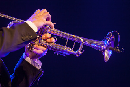 wind instrument: Male musician blowing wind instrument trumpet on stage
