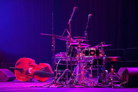 bass drum: Drum kit and double bass on stage lit by red light