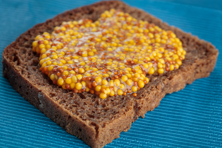 wholegrain mustard: Slice of rye bread with wholegrain mustard. Shallow depth of field