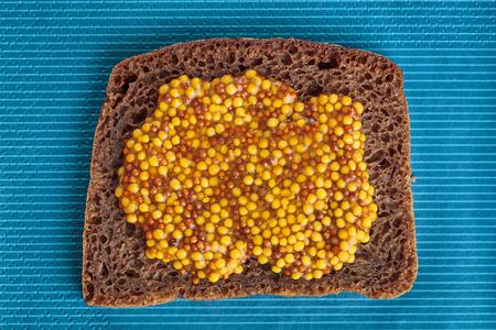 wholegrain mustard: Slice of rye bread with wholegrain mustard over blue striped background