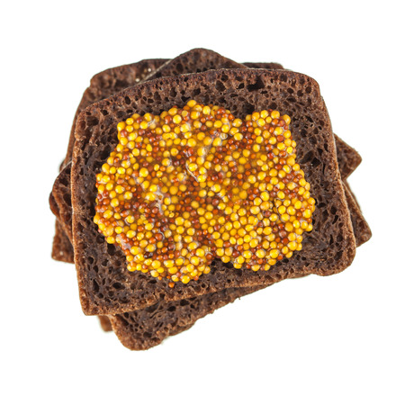 wholegrain mustard: Rye bread slices topped with wholegrain mustard isolated over white background