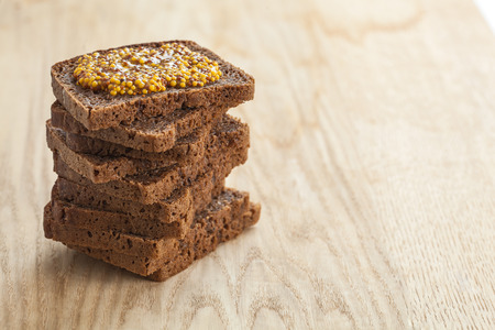 wholegrain mustard: Rye bread slices topped with wholegrain mustard. Shallow depth of field Stock Photo