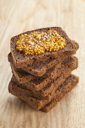 wholegrain mustard: Closeup of rye bread slices topped with wholegrain mustard. Shallow depth of field