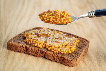 wholegrain mustard: Rye bread slice with full spoon of wholegrain mustard over it