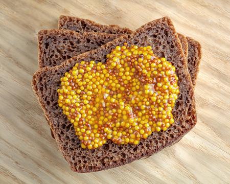wholegrain mustard: Rye bread slices  with wholegrain mustard on top Stock Photo