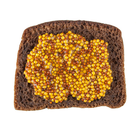 wholegrain mustard: Rye bread slice topped with wholegrain mustard isolated over white