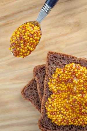 wholegrain mustard: Wholegrain mustard spoon by rye bread slices