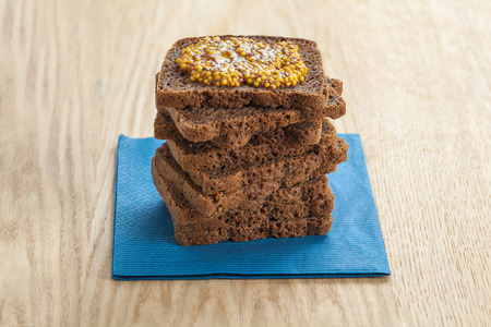 wholegrain mustard: Rye bread slices topped with wholegrain mustard on blue napkin