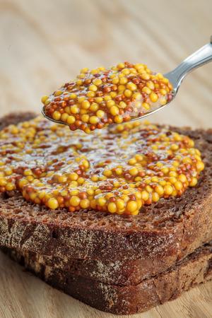 wholegrain mustard: Spoon of wholegrain mustard on top of rye bread slices