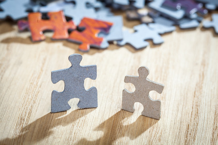 jigsaw pieces: Closeup of two jigsaw puzzle pieces on table. Shallow depth of field Stock Photo