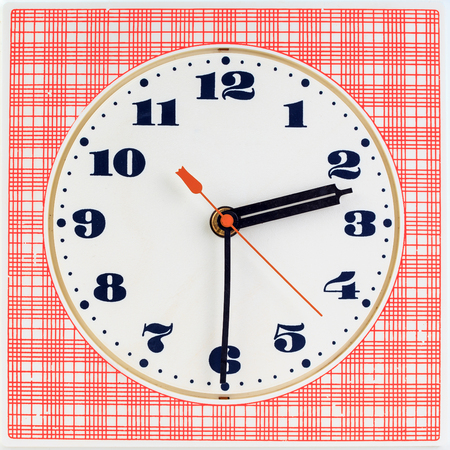 two and a half: Round clock face on red striped background showing half past two oclock Stock Photo