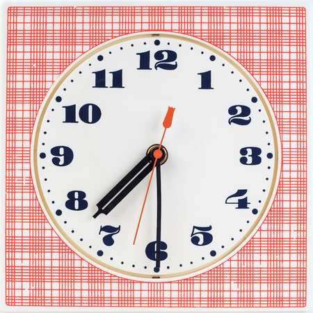 seven o'clock: Round clock face on red striped background showing half past seven oclock