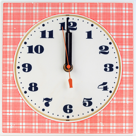 Round clock face on red striped background showing twelve oclock