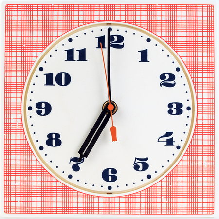 seven o'clock: Round clock face on red striped background showing seven oclock Stock Photo