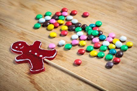 uomo rosso: caramelle pulsante del colore e la forma uomo rosso lecca-lecca sulla superficie del tavolo di legno