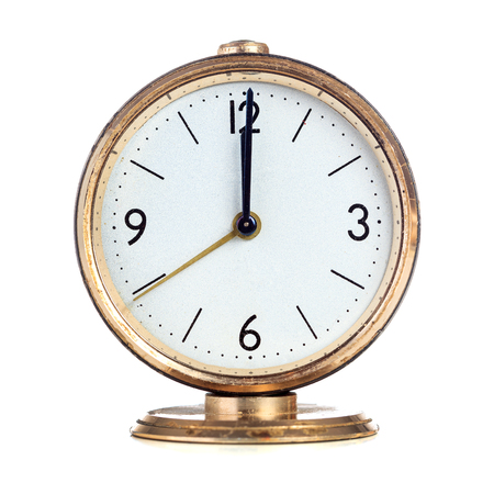 past midnight: Vintage mechanical alarm clock showing twelve oclock isolated over white