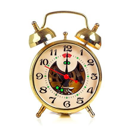 seven o'clock: Vintage golden alarm clock on white background showing seven oclock