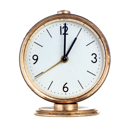 past midnight: Vintage mechanical alarm clock showing one oclock isolated over white