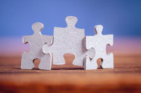 Drie puzzelstukken op tafel gezamenlijke samen over blauwe achtergrond. Ondiepe scherptediepte