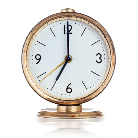 seven o'clock: Vintage mechanical alarm clock showing seven oclock isolated over white