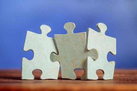 Drei Puzzlestücke auf einem Tisch Gelenk zusammen über blauem Hintergrund. Geringe Schärfentiefe