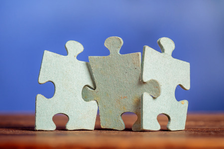 Trois pièces de puzzle sur un joint de table ensemble sur fond bleu. Faible profondeur de champ