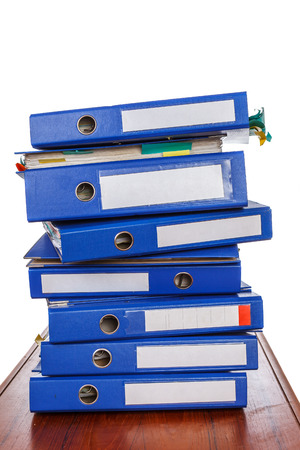 dossier: Stack of blue office folders with blank labels on desk
