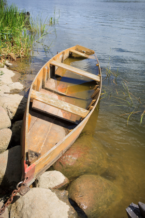 Half drowned wooden rowing boat by river board