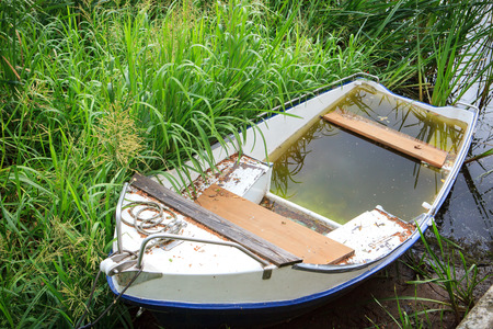 color silence: White rowing boat full of water on the river shore by green grass Stock Photo