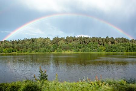 Regenboog boog over bomen door het meer