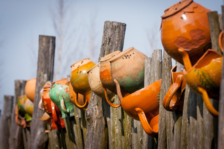 clay pots: Clay pots on the wooden fence. Shallow depth of field Foto de archivo