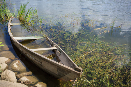 drowned: Drowned wooden rowing boat on river shore grass Stock Photo