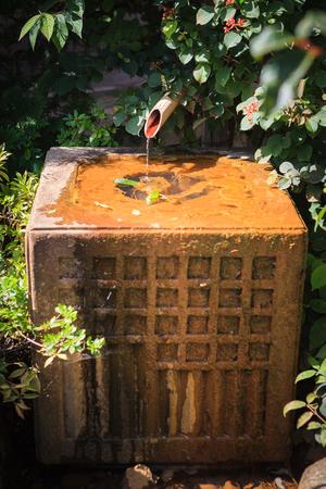 Tsukubai. Japanese style traditional bamboo fountain in garden Stock Photo