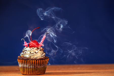 Birthday cupcake with two blown out candles and a red cherry on top over deep blue background in a cloud of a smoke