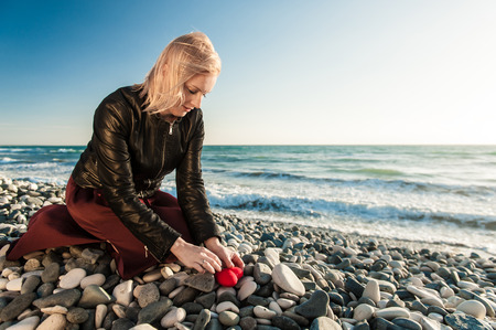 parting the sea: Blond Girl on the seaside hiding a heart