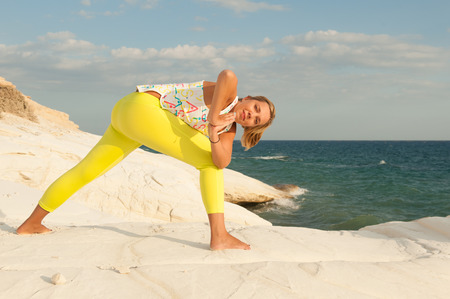 side angle pose: Young women doing yoga by the sea - Revolved side angle pose with namaste (Parivritta Parsvokonasana)