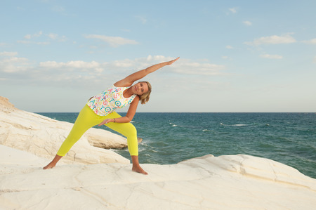 trikonasana: Young women doing yoga by the sea - Bikram triangle pose (Trikonasana Bikram)