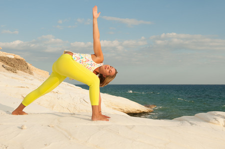 side angle pose: Young women doing yoga by the sea - Revolved side angle pose (Parivritta Parsvokonasana)