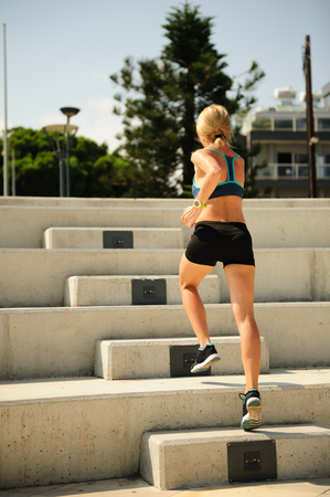 Young athletic woman exercising outdoors: running up the stairs Stock Photo