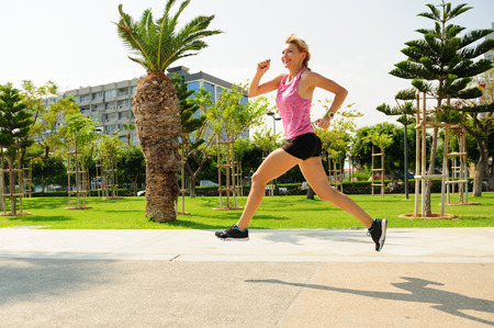 Young athletic woman exercising outdoors: running Stock Photo
