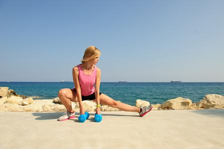 屋外で運動運動女性: 側に突進する柔軟性と強度の体重に 写真素材