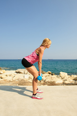 Young athletic woman exercising outdoors: deadlift for lower body strength Stock Photo