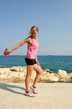 Young athletic woman exercising outdoors: tricep extensions for upper body strength