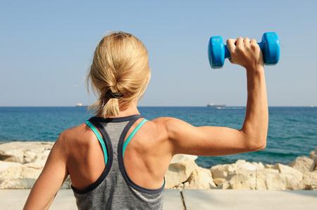 Junge athletische Frau, die draußen trainiert: obenliegende Presse für Oberkörperstärke Standard-Bild - 84787148