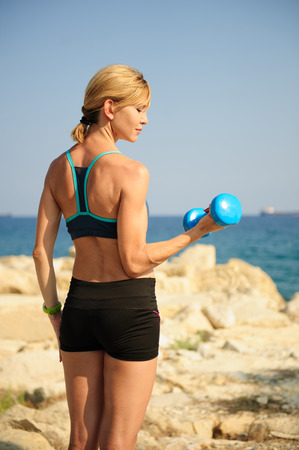 Young athletic woman exercising outdoors: bicep curl for upper body strength