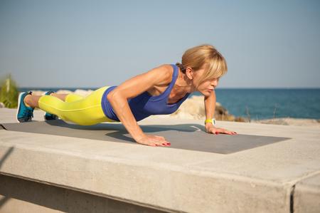 屋外で運動運動女性: 上体の強さの腕立て伏せ