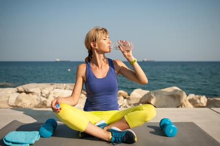 屋外で運動運動女性: 水を飲む、水 rehydratation の壊れ目