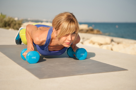 Young athletic woman exercising outdoors: pushups for upper body strength